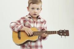 Lustiger Kinderjunge mit Gitarre moderner Bauernjunge, der Musik spielt Lizenzfreies Stockfoto