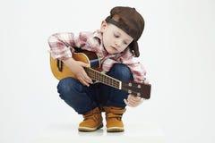Lustiger Kinderjunge mit Gitarre Ukulelegitarre moderner Bauernjunge, der Musik spielt Stockfotografie