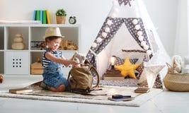 Lustiger Kindermädchentourist mit Weltkarte, Rucksack und Vergrößerungsglas Lizenzfreies Stockfoto