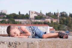 Lustiger kleiner Junge, der auf einem Betonblock auf einem Hintergrund von Hafengebäuden liegt Lizenzfreie Stockbilder
