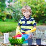Lustiger kleiner Junge, der Blumen im Garten des Ausgangs im Garten arbeitet und pflanzt Stockbilder