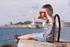 Lustiger kleiner Junge, der den Abstand durch Ferngläser untersucht Stockfoto