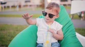 Lustiger kleiner Junge, der in der großen Sonnenbrille sitzt im Taschenstuhl am Park im Sommer ist Halten eines Glases und Tanzen stock video footage