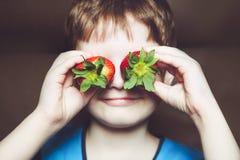 Lustiger kleiner Junge, der eine Erdbeere hält Lizenzfreies Stockfoto
