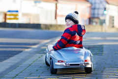 Lustiger kleiner Junge, der großes Spielzeugauto fährt und Spaß, draußen hat Stockfotos