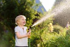 Lustiger kleiner Junge, der mit Gartenschlauch im sonnigen Hinterhof spielt lizenzfreie stockfotografie