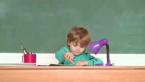 Lustiger kleiner Junge, der oben auf Tafel zeigt Schulkinder Freundliches l?chelndes Kind an der Tafel Ausbildung wenig stock video footage