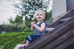 Lustiger kleiner Junge ein Jahr, sitzend auf dem Portal eines Land hou Lizenzfreies Stockbild