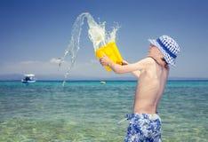 Lustiger kleiner Junge mit einem Panama, das im Meer spielt Lizenzfreie Stockfotos
