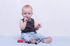 Lustiger kleiner Junge mit Gebäudewerkzeugen in seinem Mund Stockfotografie