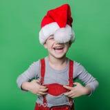 Lustiger kleiner Junge mit Santa Claus-Hutlachen Weihnachtsniederlassung und -glocken Lizenzfreies Stockfoto