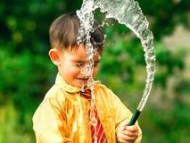Lustiger kleiner Junge schickte versehentlich einen Schlauch mit Wasser zu seinem Gesicht Stockfotografie