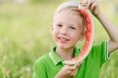 Lustiger kleiner Kleinkindjunge mit den blonden Haaren Wassermelone draußen essend Stockbild