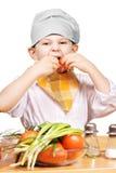 Lustiger kleiner Koch, der Tomaten isst stockfotografie