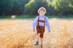 Lustiger Kleinkindjunge in den ledernen shors, gehend durch Weizen-FI Stockbild