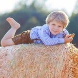 Lustiger Kleinkindjunge, der auf Heustapel und -c$lächeln liegt Stockfoto