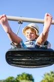 Lustiger Kleinkindjunge, der Spaß auf Schwingen hat Lizenzfreies Stockbild