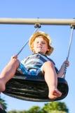 Lustiger Kleinkindjunge, der Spaß auf Schwingen hat Stockfoto