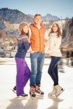 Lustiger Leuteeislauf der Gruppe im Freien an der Eisbahn Lizenzfreie Stockfotos