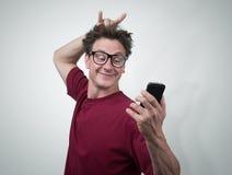 Lustiger Mann, der auf einem Smartphone sich fotografiert Stockfotografie