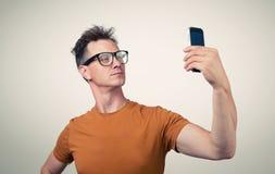 Lustiger Mann, der auf einem Smartphone sich fotografiert Stockfotos