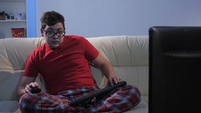 Lustiger Mann, der ein Computerspiel sitzt auf großer Couch spielt stock video