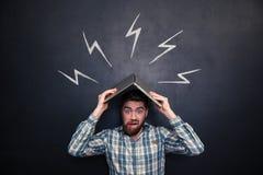 Lustiger Mann, der Laptop über Kopf über Hintergrund der Tafel hält Stockbilder