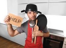 Lustiger Mann, der Wanne mit Topf auf dem Kopf im Schutzblech an der Küche bitten um Hilfe hält Lizenzfreies Stockbild