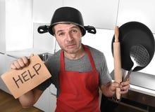 Lustiger Mann, der Wanne mit Topf auf dem Kopf im Schutzblech an der Küche bitten um Hilfe hält Lizenzfreies Stockfoto