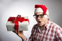Lustiger Mann in einem Hut Sankt mit einem Weihnachtsgeschenk in seiner Hand Lizenzfreie Stockbilder