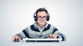 Lustiger Mann mit Kopfhörern vor Computer Stockfotos