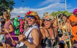 Lustiger Mann und Frau von Bloco Orquestra Voadora, das Trommel und Posaune spielt, auf den Hintergrund anderer Musiker singt und Lizenzfreie Stockfotos