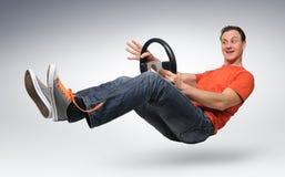 Lustiger Mannautotreiber mit einem Rad Stockfoto