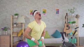 Lustiger Mannverlierer tut Eignung zu Hause mithilfe der Gummibänder langsames MO stock footage