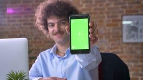 Lustiger nerdy Chef mit dem gelockten Haar des Volumens schreibend am Telefon und Anzeige in die Kamera zeigend, sitzend im moder stock video