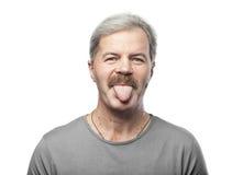 Lustiger reifer Mann zeigt die Zunge, die auf Weiß lokalisiert wird Stockfotografie
