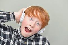 Lustiger roter behaarter Junge mit Kopfhörern Stockfotos