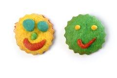 Lustiger smiley stellt die bunten Biskuite gegenüber Stockfoto