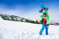 Lustiger Snowboarder, der Mädchen auf seinen Schultern hält Stockbild