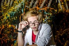 Lustiger Teenager, der wie ein verrückter Professor oder ein Student aufwirft Stockfotos