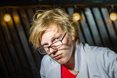 Lustiger Teenager, der wie ein verrückter Professor oder ein Student aufwirft Stockfotografie