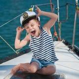 Lustiger tragender Kapitänhut des kleinen Jungen, der an Bord des Luxusbootes sitzt lizenzfreies stockfoto