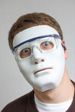 Lustiger und verrückter Kerl mit einfacher weißer Maske Stockfotografie