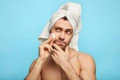 Lustiger verwirrter Mann, der sein Gesicht mit Wattestäbchen säubert lizenzfreie stockbilder
