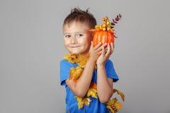 lustiger weißer blonder kaukasischer Junge kleidete mit Herbstgelbblättern für Halloween an Stockfotografie