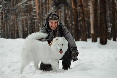 Lustiger weißer Hund gehen in den Winter in einem schneebedeckten Wald stockbild