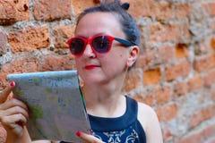 Lustiger weiblicher Tourist mit Karte Lizenzfreie Stockfotografie