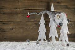 Lustiger Weihnachtshintergrund des Holzes mit Schnee und einem Sankt-Hängen Lizenzfreie Stockfotos