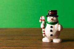 Lustiger Weihnachtsschneemann auf Holztisch- und Grünhintergrund Th stockfotos