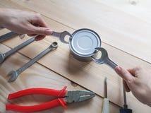 Lustiges Öffnungseingemachtes Das lustige Aussenseitermädchen, das zu einfachem versucht, öffnen eine Blechdose mit einem Schlüss lizenzfreie stockfotografie